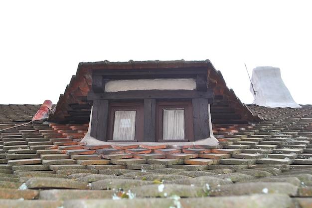 Маленькое мансардное окно на черепичной крыше старого дома и дымоход