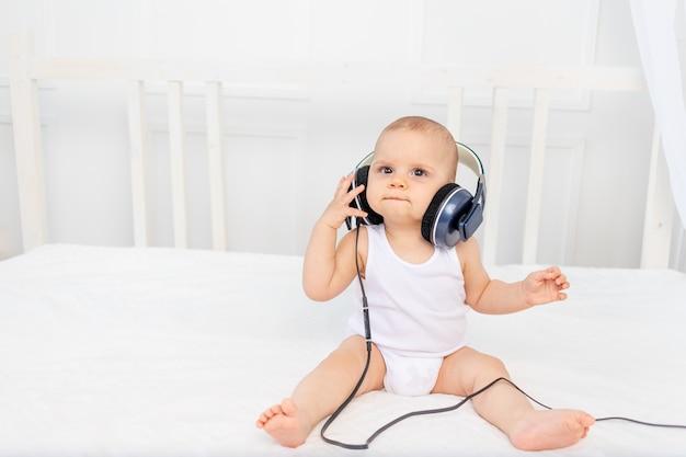 Маленький мальчик 8 месяцев сидит на кровати в детской комнате с наушниками и слушает музыку