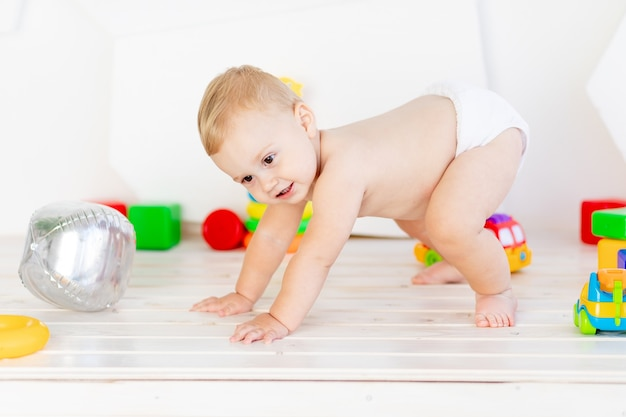 A small baby boy  crawls through in a light white nursery in diapers among toys