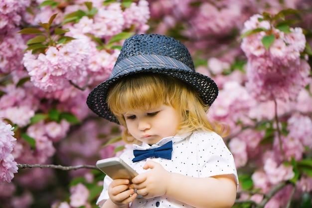 春のピンクの花の花で携帯電話で遊んでいるブロンドの髪と蝶ネクタイと白いシャツとレトロな帽子の小さな男の子