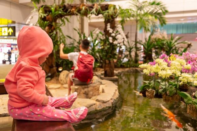 분홍색 까마귀를 입은 작은 아기 아이가 공항에 앉아 있습니다. 소녀 유아는 신중하게 수족관 분수를 보고 있습니다.