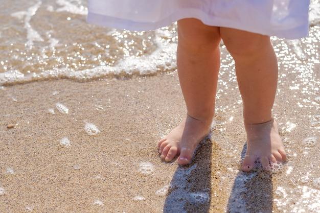 海のビーチの砂の上に小さな赤ちゃんの足のクローズアップ。海水が足を洗います。幸せな子供時代。海で休む。夏の晴れた日。スペースをコピーします。