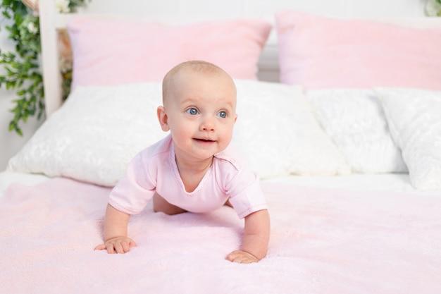작은 아기 소녀 6 개월 분홍색과 흰색 침대에 크롤링, 멀리보고