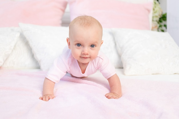 Small baby girl 6 months old crawling on a white and pink bed at home, looking at the camera, place for text