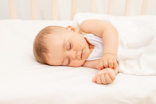 白いベッドで眠っている生後6ヶ月の小さな女の赤ちゃん、健康な赤ちゃんの睡眠