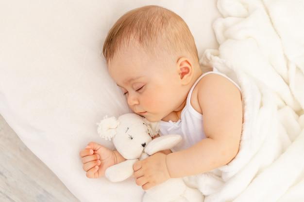 Маленькая девочка 6 месяцев спит в белой кровати, здоровый ребенок спит