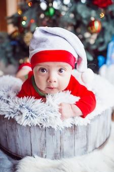 The small baby lies near christmas tree