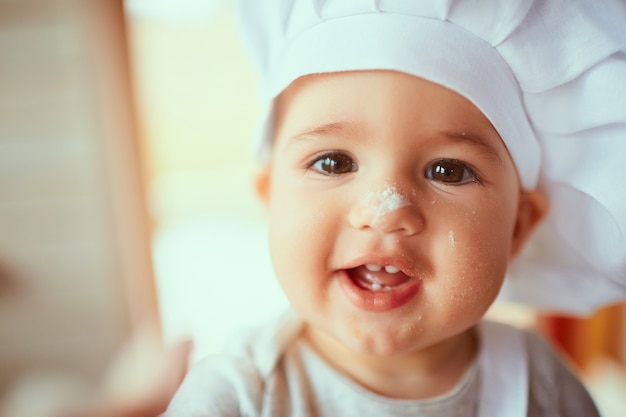The small baby  playing with flour