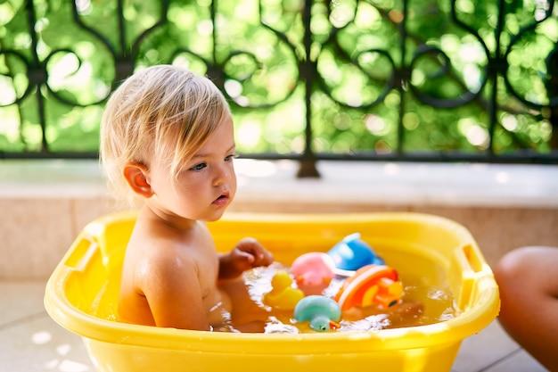 작은 아기는 발코니에 물과 장난감이 있는 분지에 앉아 있다