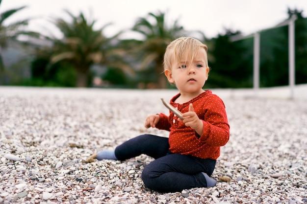 小さな赤ちゃんが小石のビーチに座って、手に棒を持っています