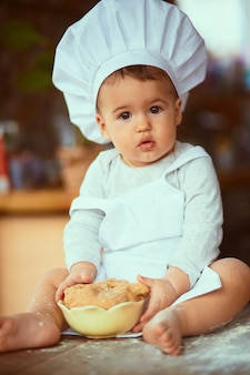 The small baby sitting  on the table and playing with dough