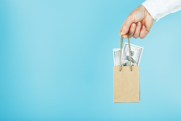 A small bag made of paper in an outstretched hand with us dollars