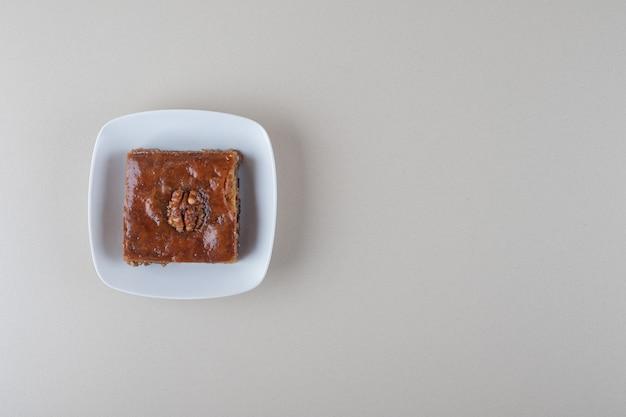 Малая пахлава на блюде на мраморном фоне.
