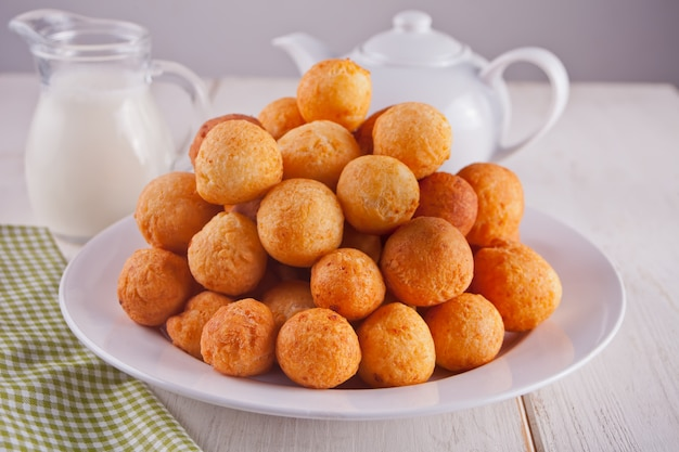 Small balls of freshly baked homemade cottage cheese doughnuts in a plate on a white background.