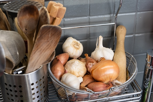 Small basket in the kitchen next to the utensils with garlic, onions and shallots.
