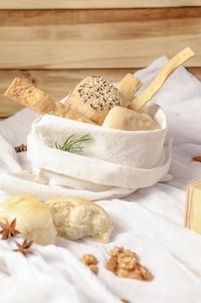 中に白いパンが入った白い布ナプキンで作られた小さなバスケット。