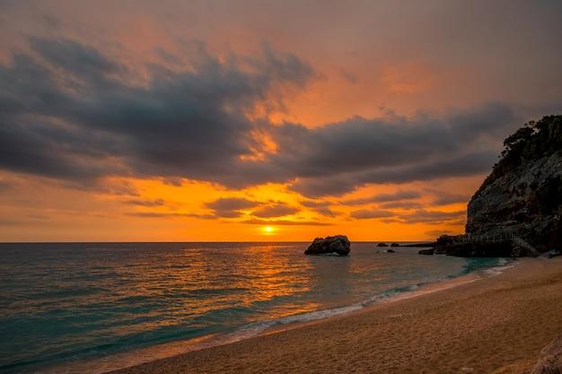 地中海のギリシャの海岸の崖の間の小さなビーチ。穏やかな水の上にカラフルな日の出