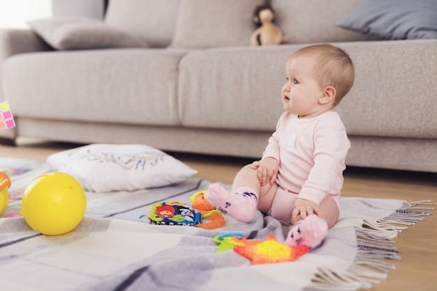 A small beautiful baby sits on the floor and plays.