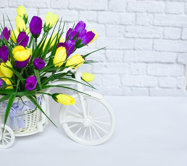 Малый красивый декоративный велосипед с желтыми и фиолетовыми цветками на белой предпосылке.