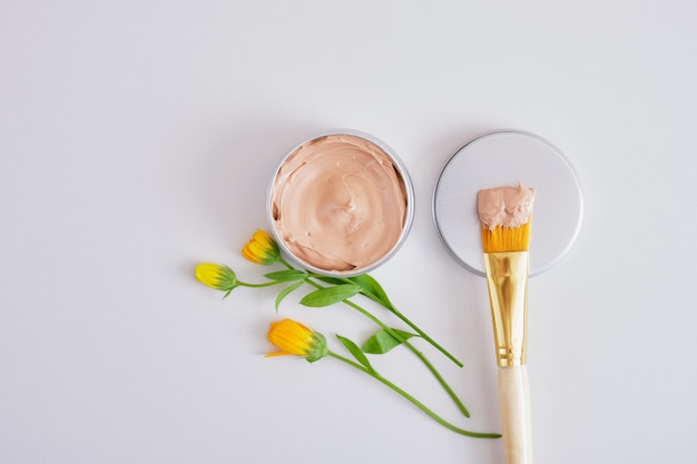 Small beautiful flowers, makeup brush and cosmetic red clay in an aluminum jar, natural cosmetics