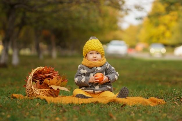 Маленькая красивая девушка в стильной теплой одежде сидит на коврике на лужайке с яблоком, сидя в осеннем парке