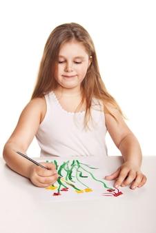 小さな美しい少女は白い背景の上に紙に花を描く