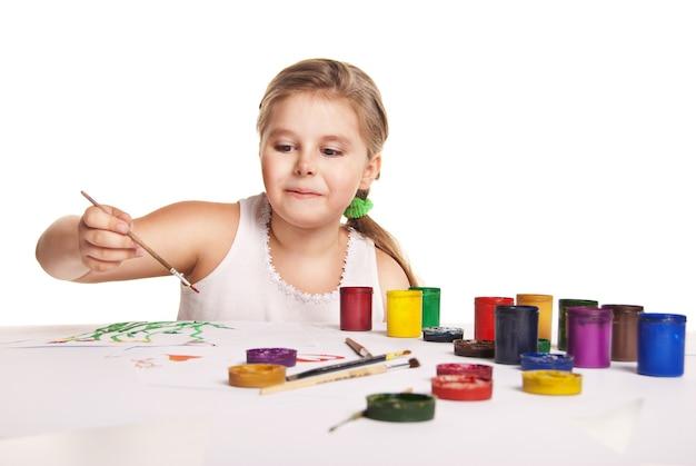 小さな美しい少女は白い背景の上の紙にペイントします