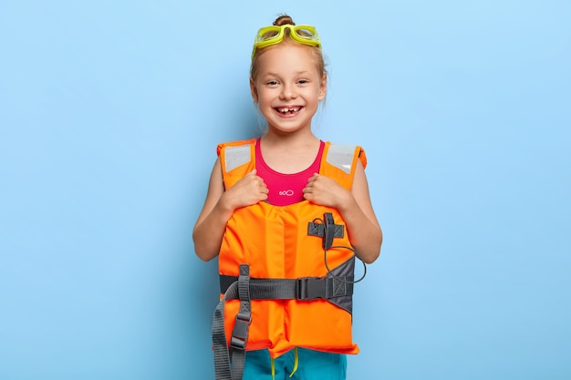 Small beautiful girl ready for boat trip, wears goggles and lifevest