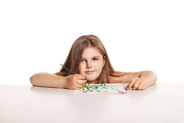 ブラシで小さな美しい少女は白い背景の上の紙に花を描く