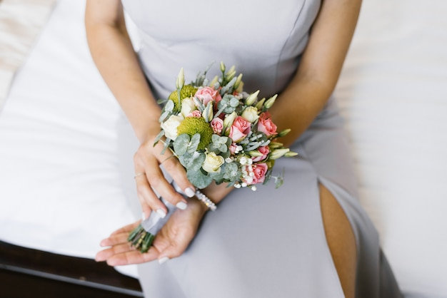 A small beautiful wedding bouquet in the hands of the bride of pink roses, white eustoma and eucalyptus branches