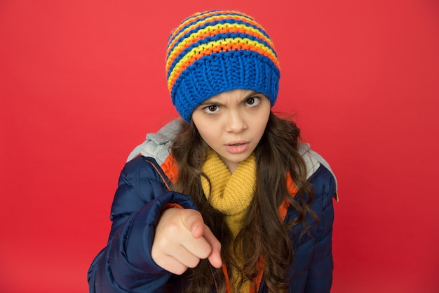 Small beauty red background. little girl puffer jacket and knitted hat. care yourself in cold weather. kid pointing finger. angry child in warm winter clothes. seasonal fashion for kids.