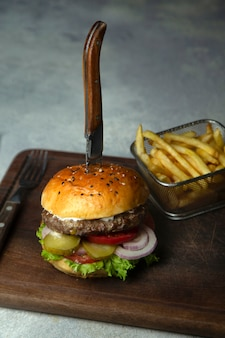 Small beef burger with pickles cucumber, onion, lettuce, tomato served with fries