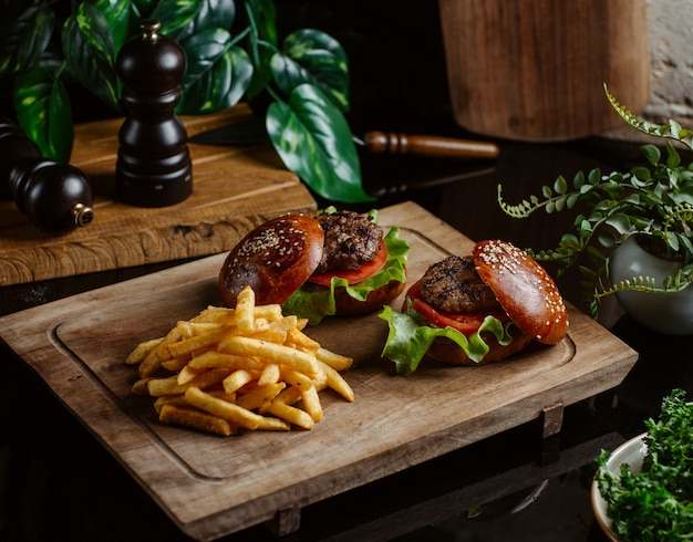 Small beef burgers without cheese on wooden board.