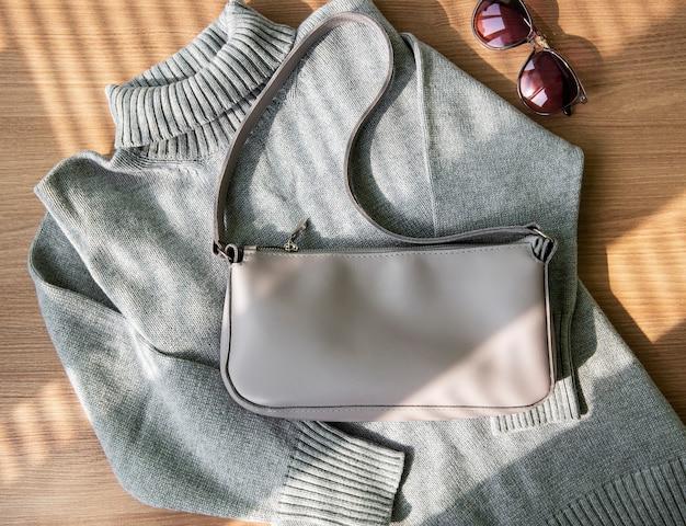 Маленькая бежевая кожаная сумка и серый свитер