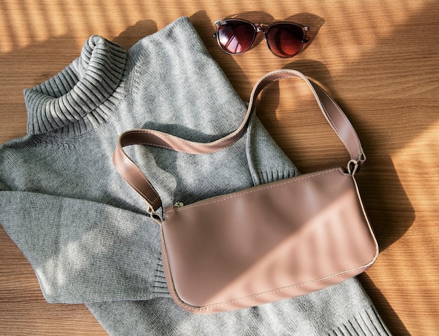Small beige leather bag and gray sweater
