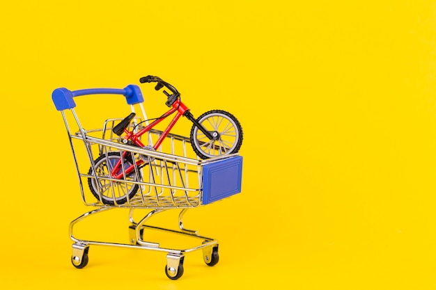 Small bicycle toy in the shopping cart against yellow background