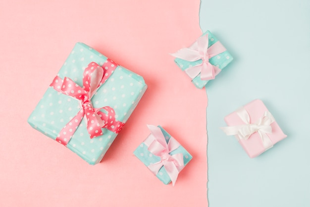Small and big decorated gift boxed tied with ribbon arrange on peach and blue wallpaper