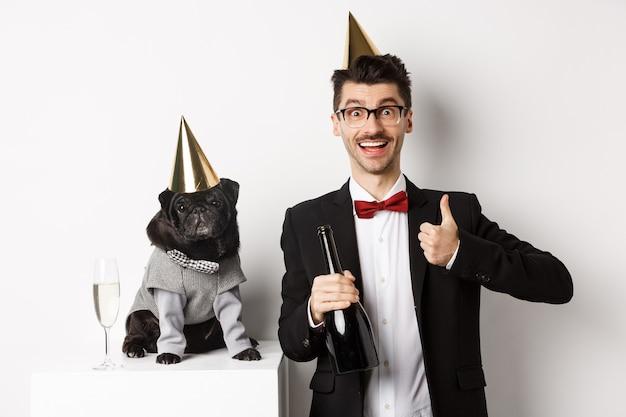 파티 모자를 쓰고 휴일을 축하하는 행복한 남자 옆에 서 있는 작은 검은 개, 엄지손가락을 위로 들고 샴페인 병, 흰색 배경을 들고 있는 소유자.