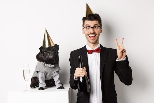 Piccolo cane nero con cappello da festa e in piedi vicino a un uomo felice che celebra le vacanze, proprietario che mostra segno di pace e tiene in mano una bottiglia di champagne, sfondo bianco.