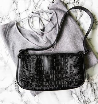 小さな黒い革のバッグと灰色のセーター