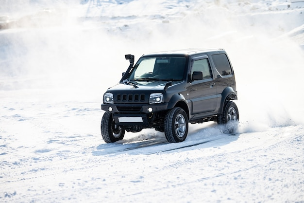 Small black suv rally race at frozen river in winter