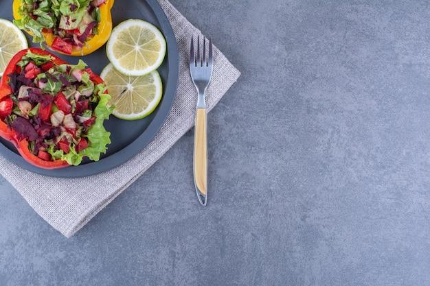Маленький черный поднос с ломтиками лимона и двумя порциями салатов в ломтиках перца на мраморной поверхности