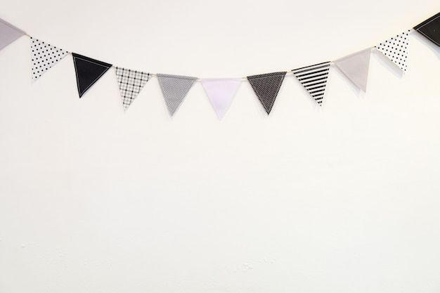 Small black white triangle shape flag hanging curve down plaster wall