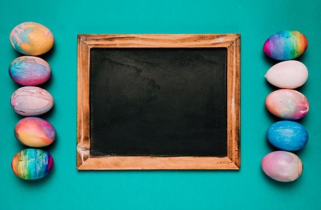 緑色の背景でカラフルなイースターエッグの行の間の小さな黒板