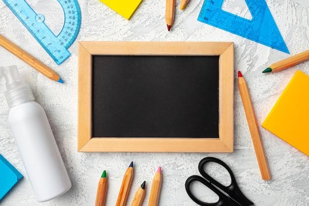 Маленькая доска в деревянной рамке в окружении цветных карандашей, плоская планировка