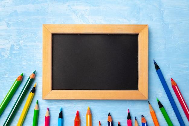 Маленькая доска в деревянной рамке в окружении цветных карандашей, вид сверху