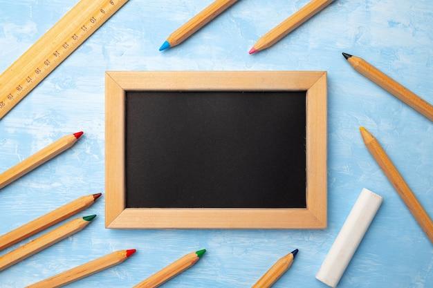 Маленькая классная доска в деревянной рамке в окружении цветных карандашей