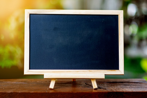 A small blackboard placed on a wooden table the back is a green tree. for educational illustration