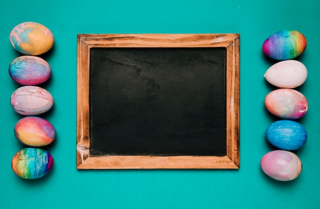 Small blackboard between the row of colorful easter eggs on green background