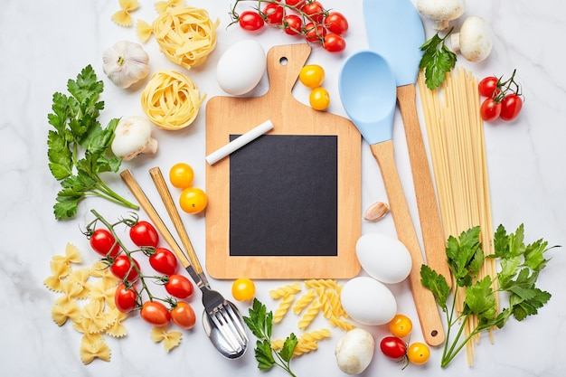 Small blackboard with copy space surrounded by ingredients for cooking different types of pasta, condiments, utensils, healthy raw vegetables scattered light marble background